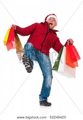 Full length portrait of a young man in winter clothing and Santa hat with shopping bags slipping on floor isolated on white background