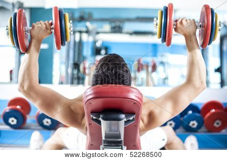 Back view of a stong man lifting weights in the gym