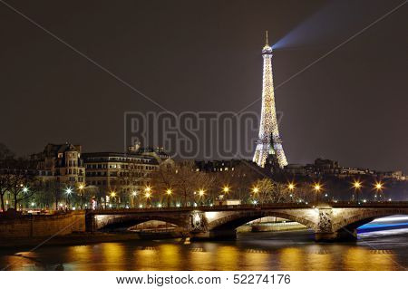 PARIS - APRIL 03: Eiffel Tower with night illumination and Pont des Invalides on April 03, 2013 in Paris, France. The Eiffel tower is the most visited touristic attraction in France
