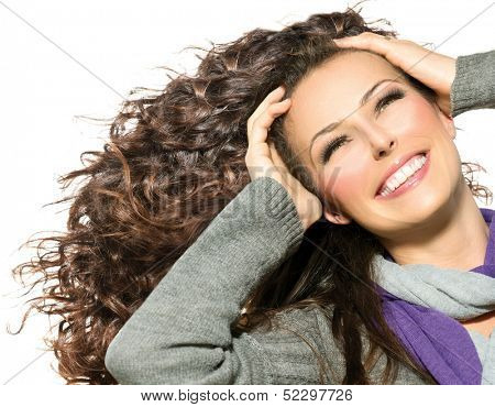 Beauty Woman with Long Curly Hair. Healthy Blowing Hair and Beautiful Smile