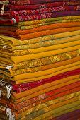 Arabian carpets piles up in a Marrakech shop poster
