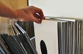 Browsing through vinyl records collection. Music background. poster