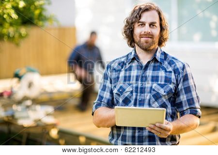 Portrait of mid adult manual worker holding digital tablet with coworker working in background at construction site