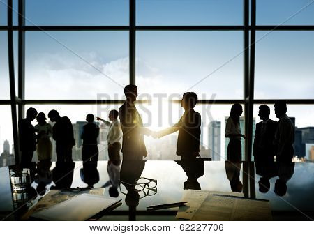 Group of business people and men handshake reflected onto table with documents.