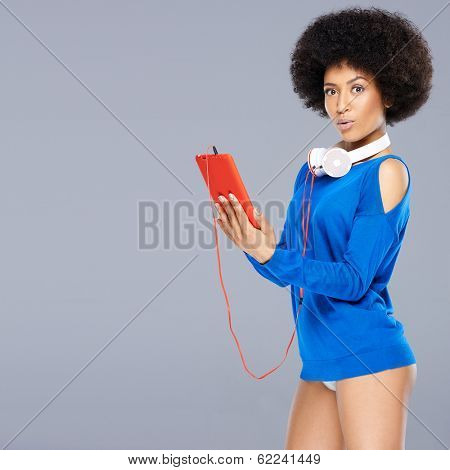 Stunning African American woman with a curly afro hairstyle wearing only a blue top posing with a flirtatious look holding a music storage device with headphones around her neck on grey with copyspace
