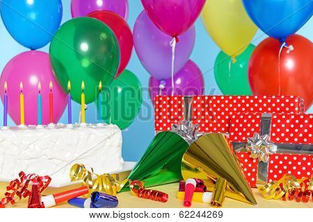 Birthday party still life with cake, balloons, presents, streamers and hats.