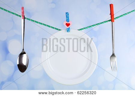 Tableware dried on rope on bright background