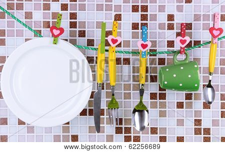 Tableware dried on rope on tile mosaic background