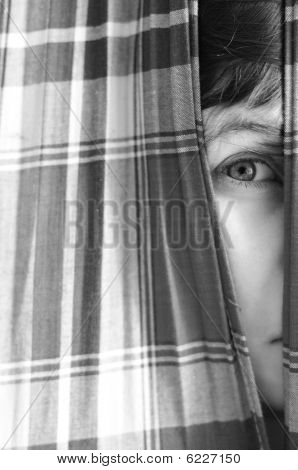 Girl Looking Through A Chink In Curtains