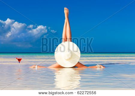 Young Woman In Straw Hat Laying At The Tropical Beach And Enjoying Cocktail