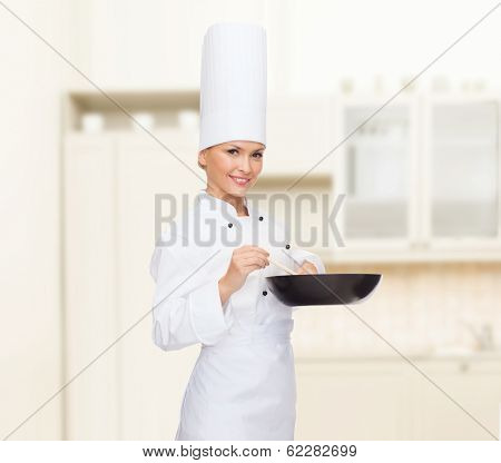cooking and food concept - smiling female chef with pan and spoon