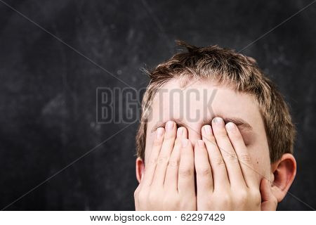 Student with his hands over his face