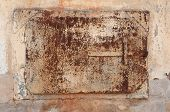 Detail yellow stucco wall with rusty iron door poster