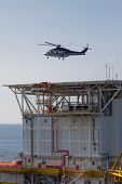 helicopter landing on an offshore oil-plant , service travel to oil and gas platform in offshore. poster