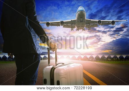 Business Man And Luggage Standing In Airport And Passenger Jet Plane Flying Over Runway Against Beau