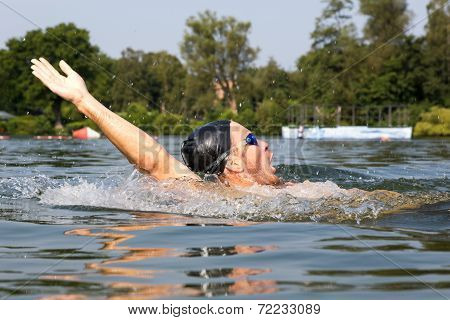 Man Swims Backstroke In A Swimming Pool