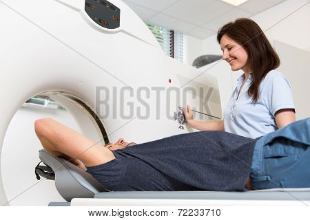 Medical technical assistant councelling patient and preparing scan of the spine with x-ray computed tomography CT in radiology poster