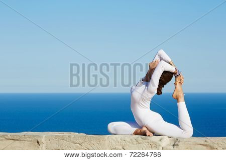 Young attractive woman with beautiful body engage yoga at high altitude on beautiful ocean backgroun