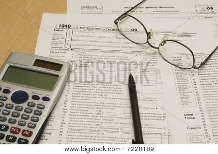 Tax forms with calculator, glasses, and pen