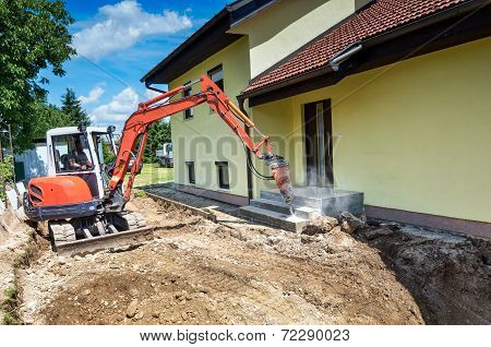 A Crusher Is Demolishing A House