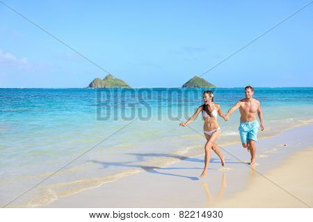 Beach travel happy vacations couple running during their holidays on white sand Hawaiian beach. Beautiful nature landscape of Lanikai, Oahu, Hawaii, USA
