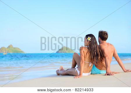 Hawaii vacation couple relaxing tanning on beach. Beautiful young adults on holidays lying down on white sand of Lanikai beach, Oahu island, Hawaii, USA.