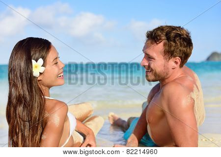 Vacation couple relaxing on beach tanning laughing talking together. Portrait of two young adults mixed race asian caucasian having fun during travel holidays.