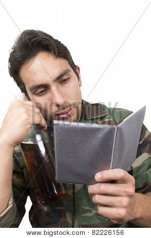 distraught military soldier veteran holding a bottle and looking at photos ptsd