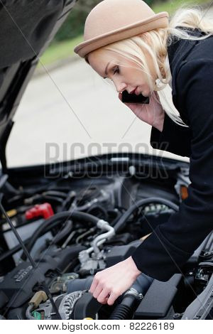 Woman being talked through roadside assistance on her broken down car on her mobile phone as she tinkers with the engine