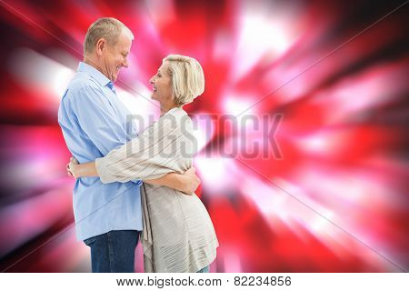 Happy mature couple hugging and smiling against valentines heart pattern