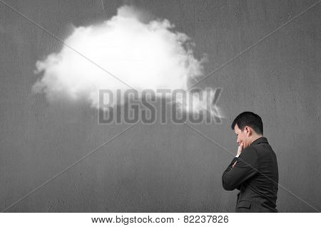 Businessman Thinking About White Cloud Thought Bubble With Concrete Wall
