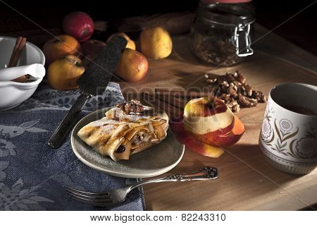 Apple strudel with walnuts and raisins served on a blue plate with apples and sticks of cinnamon and a jar of walnuts in the background. poster