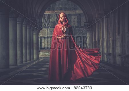 Woman with a mask wearing red cloak outdoor