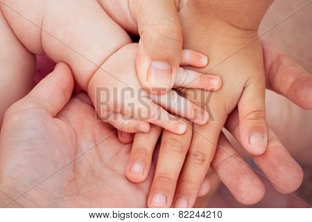 Four hands of the family. The concept of love, friendship, happiness in the family. Tinted image.Ton