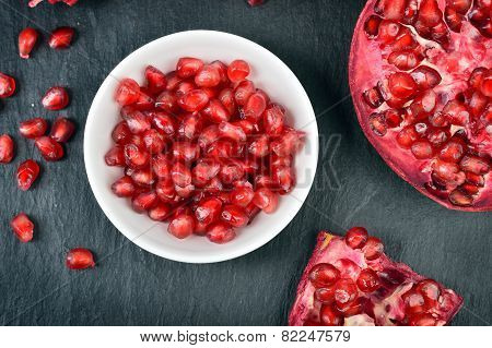 Red pomegranate seeds in a white bowl on table. Open fresh ripe pomegranate. poster