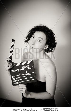 Seductive actress showing clapperboard vintage black and white vertical portrait poster