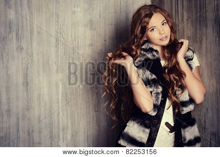 Fashion shot of a pretty teenager girl with beautiful long curly hair wearing white knitted dress and fur jacket. Beauty, fashion. poster