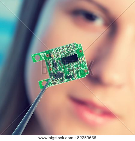 Girl shows new microchip on plate  that can be implanted into a paralyzed patient, developed a microchip muscle simulator