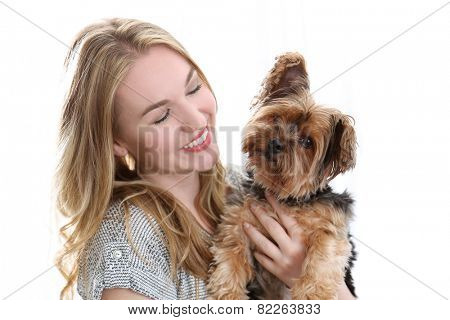 Happy young woman holding cute small dog