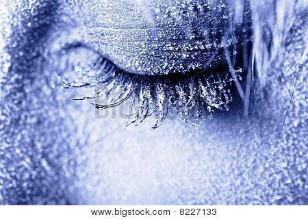 Frozen woman's eye covered in frost. Close-up shot toned in blue poster