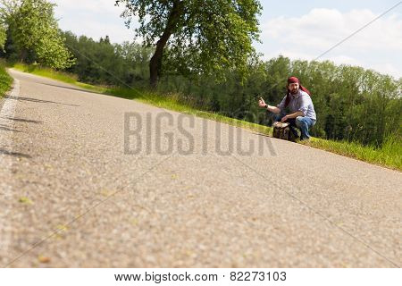 Male Hitchhiker Is Sitting On A Street