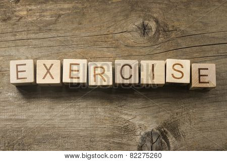exercise word in vintage wooden blocks on a wooden background