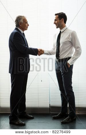 two businessmen standing up smiling