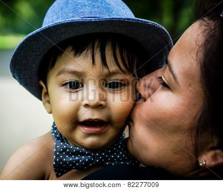 Smiling Latino Baby Being Kissed On Cheek