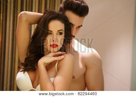Sensual woman posing in mirror with young boyfriend passionate couple poster