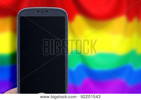 Blue smartphone and LGBT flag blur background. Idea for Valentines Day messages, LGBT love, lovers, love apps, Internet, blogs and others.