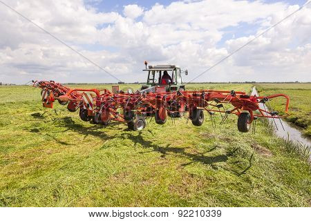 Red Hay Turner In Green Meadow In The Netherlands