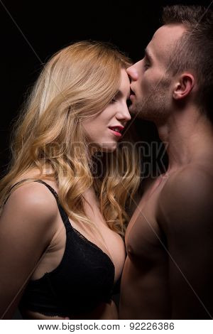 Passionate young couple in a loving embrace poster