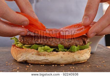 Cook adding tomato on burger.Preparing and making hamburger.