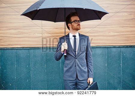 Young entrepreneur with briefcase standing outside under umbrella poster